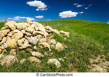 Pile of stones in Tuscany field at summer, Italy