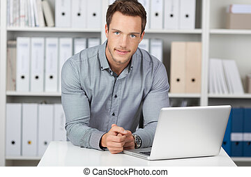 Businessman With Laptop At Office Desk - Portrait of a young...