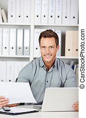 Man In Office With Laptop And Documents - Portrait of a...