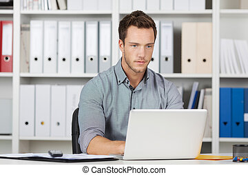 Businessman Using Laptop At Office - Serious young...