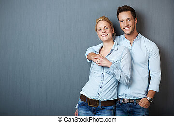 Loving Couple Against Bue Gray Background - Portrait of a...