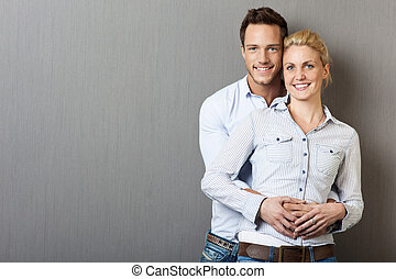 Young Happy Couple Against Gray Background - Portrait of a...
