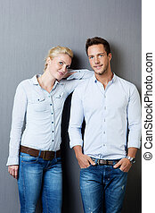 Young Cool Couple Against Gray Background - Cool young man...