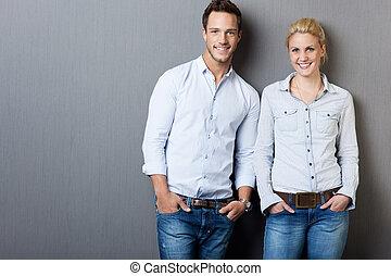 Portrait Of Smart Couple Against Gray Background - Portrait...