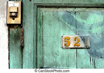 The buzzer on the vintage green wood door.