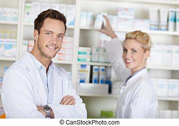 Two Smiling Pharmacists At Drugstore - Portrait of a smiling...