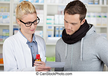 Customer Buying Medicine At The Pharmacy - Young male...