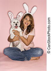 Woman and dog wearing rabbit ears. - Caucasian prime adult...
