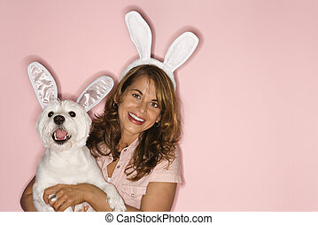 Woman and white dog wearing rabbit ears - Caucasian prime...