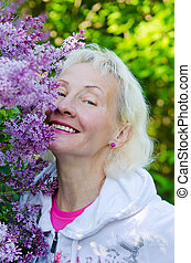 Portrait of a woman from a Bush blooming lilac
