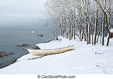 Winter landscape with a fishing boat on seacoast