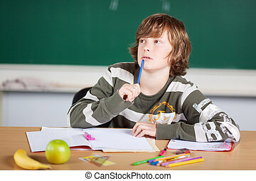 Young male student looking at something with pen on his chin