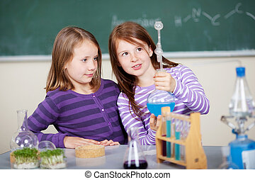 Young girls doing a chemistry experiment standing examining...