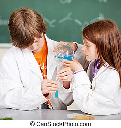 Young students learning chemistry - Young boy and girl in...