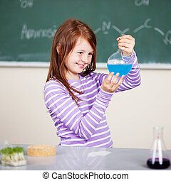 Smiling student holding a chemical formula in chemistry...