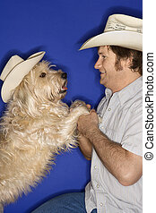 Dog and man in cowboy hats. - Fluffy brown dog and male...