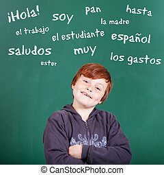 Male student learning Spanish words over the blackboard...