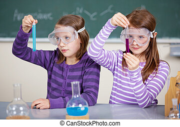 Two female students at the table with chemical reagents and...