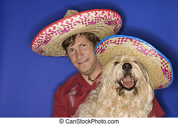 Dog and man wearing sombreros. - Fluffy brown dog and...