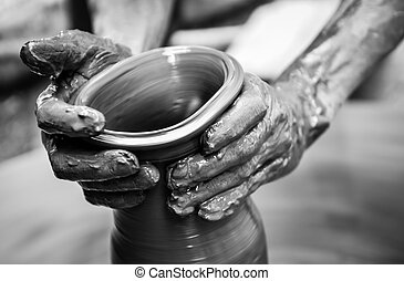 Hands of a man creating pottery on wheel, monochrome vintage...