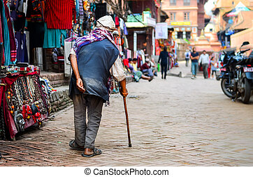 Poor old man walking with stick in exotic asian street,...