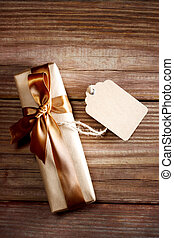 Gift box on a rustic wooden table with a blank tag - Brown...