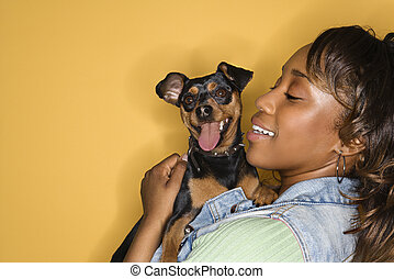 Woman holding small dog. - African American young adult...