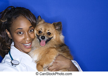 Woman veterinarian holding brown dog. - African American...
