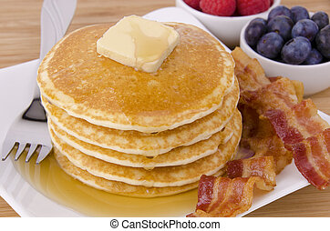 Stack of pancakes and bacon with fruits on background. Top...