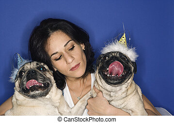 Woman holding two Pug dogs. - Caucasian prime adult female...