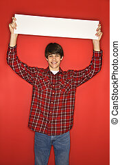 Boy holding blank sign - Portrait of Caucasian teen boy...