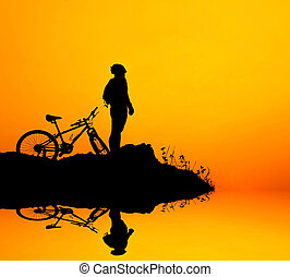 Man and bike silhouette with the sky as background