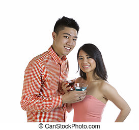 Photo of young adult couple holding mixed drinks while smiling on white background