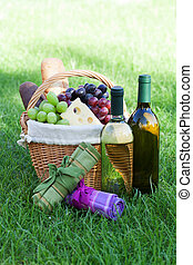 Outdoor picnic basket with wine on lawn - Outdoor picnic...