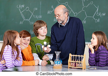 Science class - Portrait of teacher instructing students...