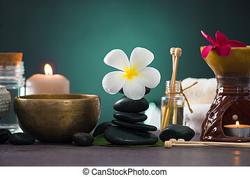 Balanced spa stones with green leaves background.