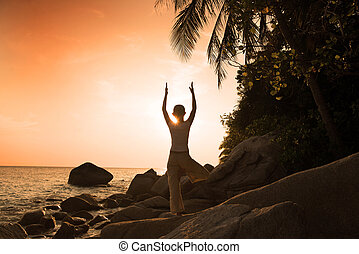 girl silhouette performing yoga on beach during a beautiful...