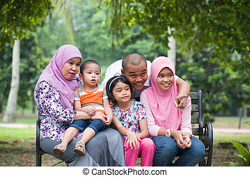 Happy Malay Asian Family enjoying family time together in...