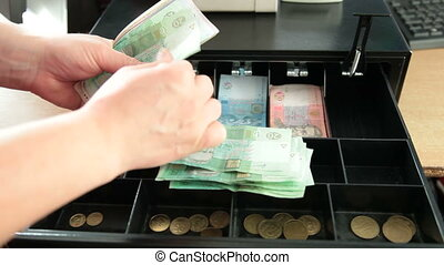 Cash register drawer - Cashier counting Ukrainian money...