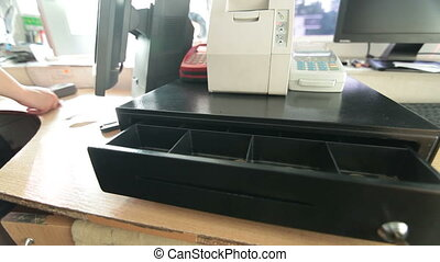Open cash register drawer with Ukraine money at gas station...
