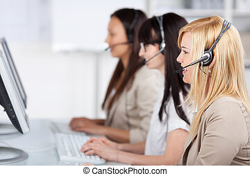 young women sitting in the office using headset - three...