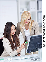 female co worker working together on computer - two young...