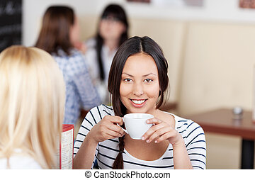 Woman Having Coffee With Friend In Cafe - Portrait of young...