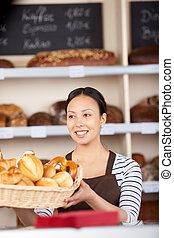 young saleswoman at work in bakery with shelves in...