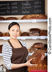 salesgirl in bakery holding wholemeal bread against shelves