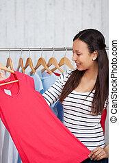 young woman choosing shirt in shop