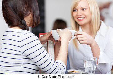 Businesswoman With Coworker Holding Coffee Cup In Cafe -...