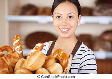 smiling salesgirl working in bakery and holding basket with...