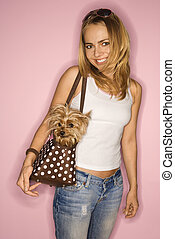 Woman with dog in bag. - Caucasian young adult female with...
