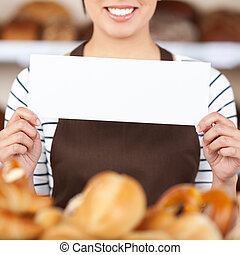 Teenage Waitress Holding Blank Sign In Cafe - Midsection of...